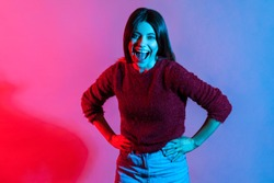 Happy emotions, hilarious laughter. Neon light portrait of joyful carefree woman holding belly and laughing out loud after hearing very funny story, good joke, anecdote. indoor studio shot isolated