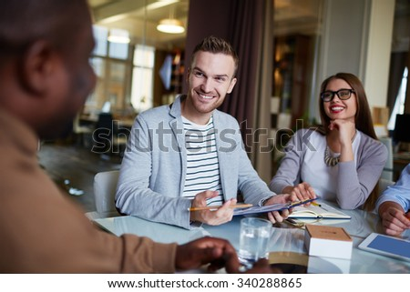 Happy employee looking at his colleague during explanation