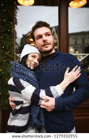 happy enamored couple is standing outdoors near the decorated shop window and hugging each other. Valentines day concept #1279332955