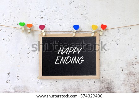 Happy ending - Concept words on the blackboard hanging with rope on rustic wooden background