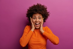 Happy energetic woman grabs face, hears wonderful news, realises she won huge money, stands impressed and speechless, dressed in orange jumper, feels lucky and thrilled, got incredible offer