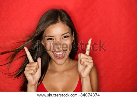 Happy energetic woman on red pointing fresh. Candid portrait of cheering beautiful young mixed race Chinese Asian / white Caucasian woman on red background.