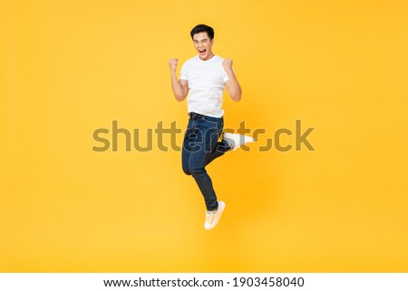 Happy energetic young Asian man jumping yelling and clenching fists isolated on yellow studio background, selective focus Сток-фото ©