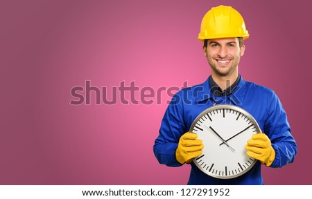 Happy Engineer Holding Wall Clock On Coloured Background