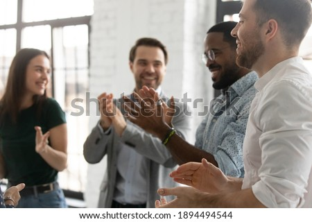 Happy enthusiastic multiracial young business people standing in modern office board room clap hands congratulating each other with successful seminar accomplishment, common victory, teamwork concept