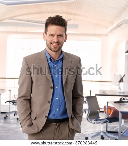 Happy entrepreneur at contemporary office, wearing suit, smiling. Stock photo ©