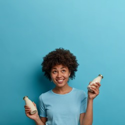 Happy ethnic curly woman drinks lactose free beverage, holds bottle of almond or coconut milk, looks upwards, smiles positively, isolated over blue background, copy space for your information