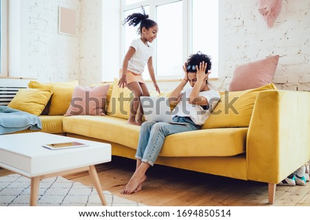Happy ethnic daughter jumping on yellow couch and disturbing exhausted and irritated mother in casual clothes holding hands on head while working at home