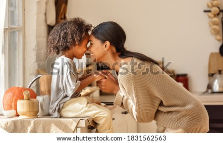 Happy ethnic family mother and little son kiss and laugh while preparing breakfast in the kitchen at home
