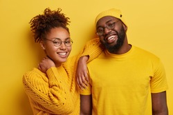 Happy ethnic sister and brother have fun together, laugs from positive emotions, wear round spectacles model against yellow background. Afro couple glad to make photo in studio. Bright color prevails