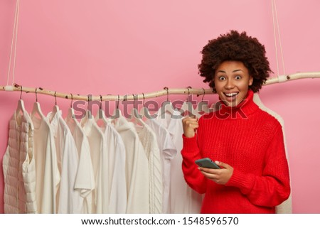 Happy ethnic woman rejoices getting free gift with purchase in clothes shop, holds cellular and clenches fist, wears red sweater, poses near rack with white clothing. Technology, wear concept