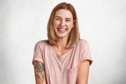 Happy European female laughs joyfully, shows white teeth, has bobbed hairstyle, dressed in casual t shirt, has tattoo, isolated over white background, recieves pleasant compliment. Emotions.