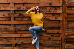 Happy european girl in winter sweater enjoying photoshoot on wooden background. Full-length shot of dreamy female model in jeans and knitted hat.