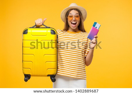 Happy European girl with suitcase and airplane tickets isolated on yellow background excited about trip #1402889687