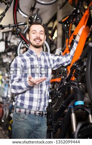 happy european man in sports workshop mounts bike using special tools #1352099444