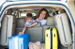 Happy European woman with her little son look back at the trunk of a car with suitcases. Family summer vacation. Traveling by car with a child. A boy with his mother in the back seat of a jeep.
