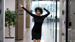 Happy excited african business woman triumphing after job interview in office. Young businesswoman cheering raising hands. Successful mixed race girl celebrating promotion or appointment with dancing