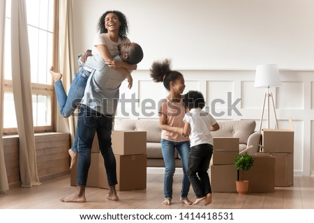 Happy excited african family celebrate moving day relocation together, cheerful black parents embrace and cute kids children jump laugh in living room with boxes, new house purchase and renovation