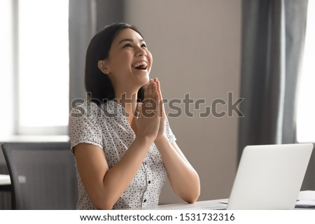Happy excited Asian businesswoman puts hands in prayer, thanking fate for business success, smiling employee celebrating great work results, student received good news, positive exam result
