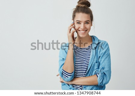 Happy excited attractive young woman calling friend spending free-time home gossiping discussing last fashion trends smiling broadly feeling joyful amused, holding smartphone, white background