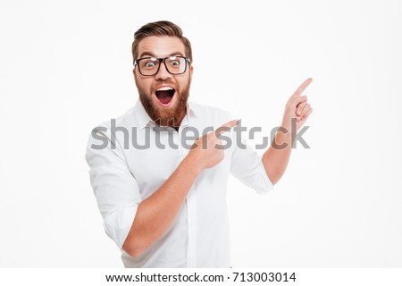 Happy excited bearded man in eyeglasses pointing away at copy space with two fingers isolated over white background