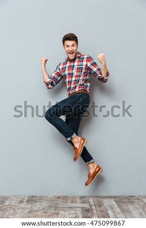 Happy excited cheerful young man jumping and celebrating success over gray background #475099867