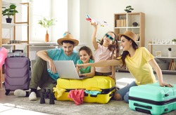 Happy excited family and daughter children buying payment for flight ticket booking hotel online using laptop with travel suitcase around at home living room. Holiday vacation traveling abroad concept