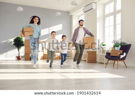 Happy excited family with unpacked boxes entering new home. Parents and little children holding hands and running to explore newly bought house or apartment. Real estate business and mortgage concept Сток-фото ©