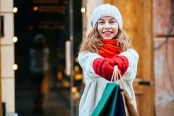 Happy excited female shopper stretching her hand holding shopping bags in front. Young girl wearing white sweater, red scarf and mittens.