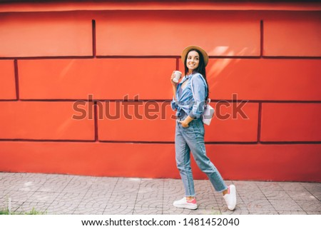 Happy excited female traveller walking around city urban setting enjoying free time for discover world, positive Ukrainian woman in trendy apparel holding takeaway cup with caffeine beverage