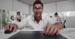 Happy excited financial broker working on laptop in office. Young indian businessman typing on computer receiving good news and feeling thrilled