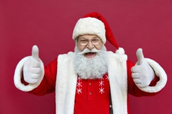 Happy excited funny bearded old Santa Claus wearing costume showing thumbs up hand like gesture looking at camera standing isolated on red background. Christmas ads recommendation choice concept.