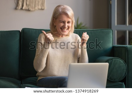 Happy excited grey haired mature woman celebrating online win, using laptop, looking at screen, sitting on couch at home, middle aged female feeling amazed, surprised by unbelievable good news