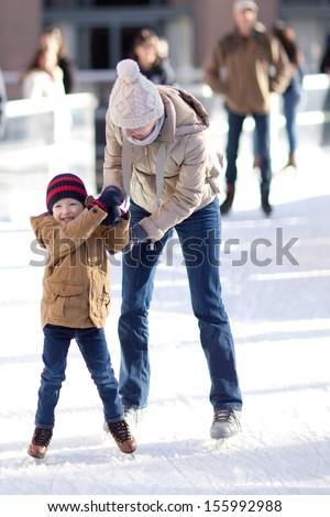 happy excited little boy and his young mother learning ice-skating