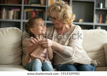 Happy excited little 6 years old cute girl enjoying learning needlework from smiling caring middle aged mature granny in eyeglasses, relaxing together on sofa at home, family hobby activity concept.