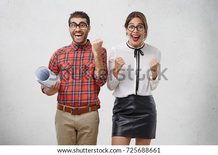 Happy excited male and female colleagues rejoice their triumph and success, raise fists with joy, succeed in presenting project to boss, share positive emotions with you. Happiness, excitement concept #725688661