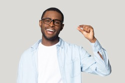 Happy excited millennial african american guy wearing eyeglasses showing with fingers small prices gesture, isolated on grey studio background. Smiling black man demonstrating little measurement.