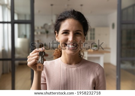 Happy excited millennial latina woman buying modern studio apartment first time look at camera pose indoors hold key in hand. Portrait of overjoyed lucky young lady win new flat as top lottery prize Stockfoto ©