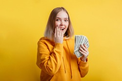 Happy excited rich young woman win money cash. Lady hold Dollar stack surprised rejoices at lottery victory. Teen girl covered her open mouth with hand surprise isolated over yellow color background