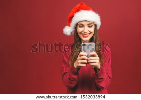 Happy excited woman in red santa claus hat with mobile phone isolated over red background. stock photo