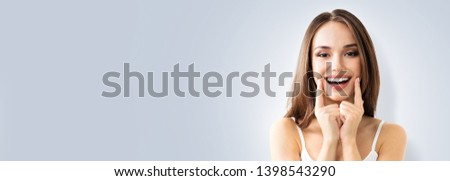 Happy excited woman showing toothy smile. Portrait of optimistic girl. Grey color background with Copy Space area, for some advertising text or slogan. Optimism or Dental Health Care concept picture.