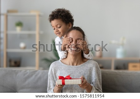 Happy excited woman sitting on couch in living room with covered by playful small preschool kid boy hands eyes, holding wrapped gift box, feeling curious. Birthday or Mothers day celebration concept.