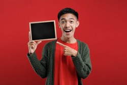 Happy excited Young Asian man holding blank small blackboard, Young Asian student smiling hold blank small blackboard, on red background