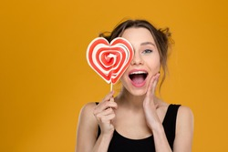 Happy excited young woman covered her eye with bright heart shaped lollipop over yellow background