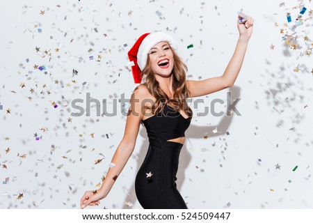 Happy excited young woman in santa claus hat dancing and laughing over white background
