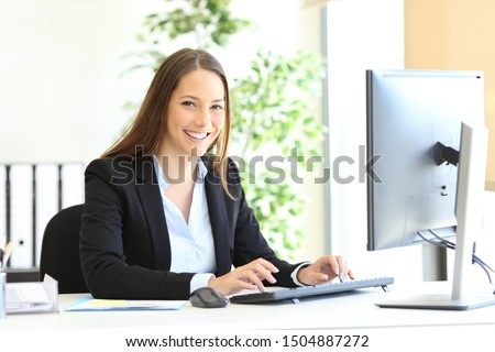 Happy executive looks at camera at office with the hands on computer keyboard at office
