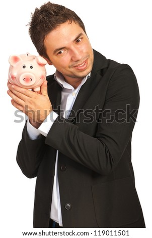 Happy executive man listening to piggy bank isolated on white background
