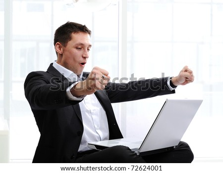 Happy executive raising fists in excitement, in front of laptop - stock photo