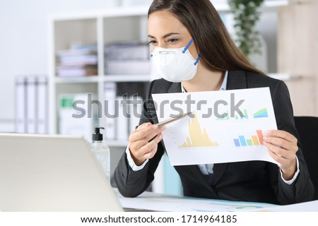Happy executive woman with protective mask shows growth graph report on videocall on laptop at the office