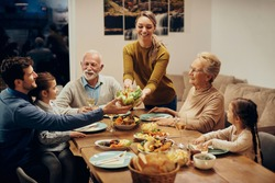 Happy extended family having a meal together at dining table. Focus is on young woman bringing salad at the table.